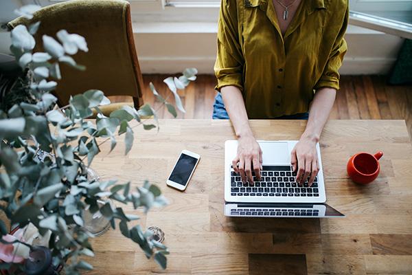 Woman typing in online gratitude journal