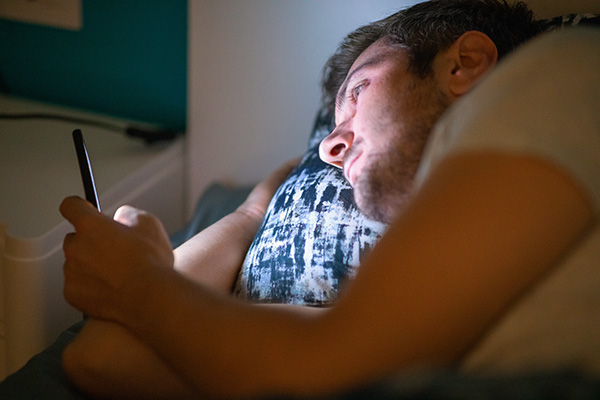 Young man lying in bed at night and using his smart phone