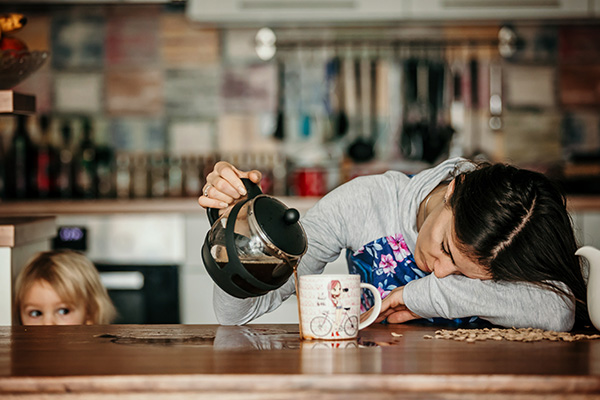 Tired mother, trying to pour coffee in the morning.