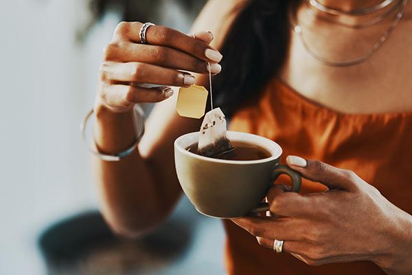 Woman holding tea cup, tea bag