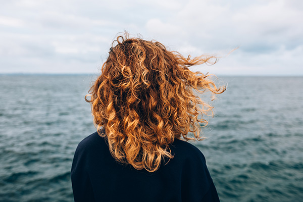 View from the back a woman with curly hair looks at the sea