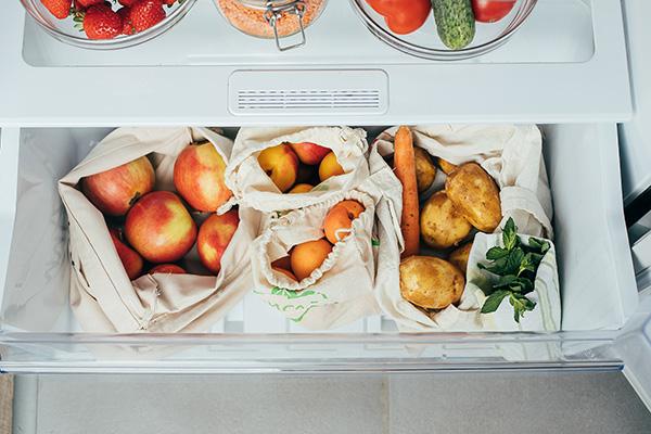 Bolsas reutilizables de verduras, frutas en nevera.