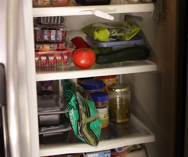 Vista del refrigerador abierto lleno de comida