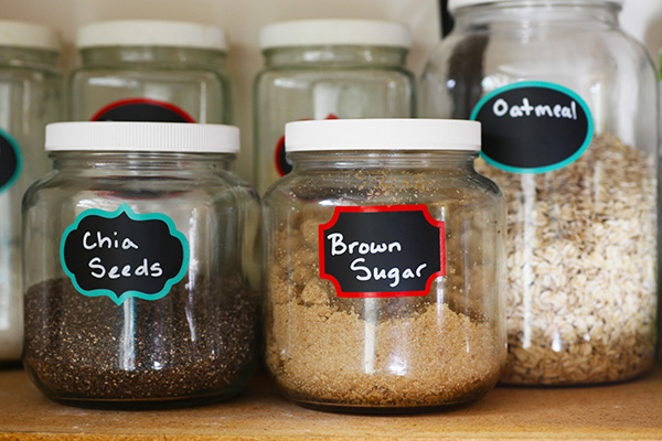 Glass jars filled with kitchen staples on pantry shelf.