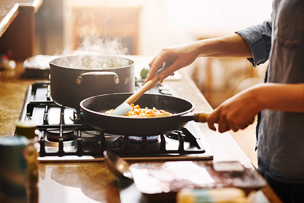 Woman stirring vegetables in a pan