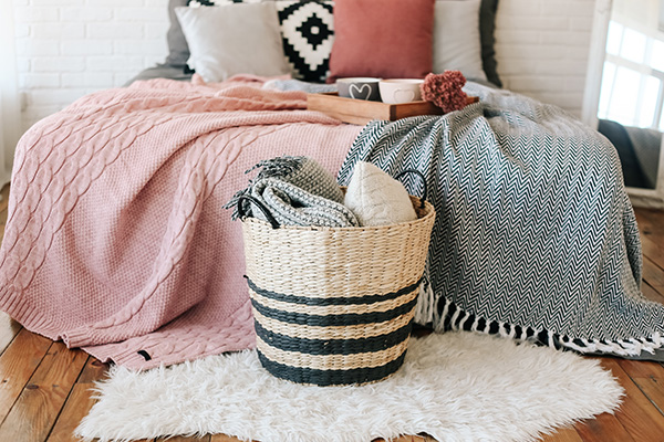 Blankets on bed, pillows in basket