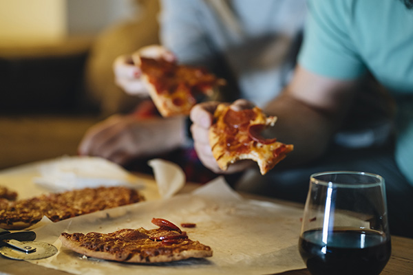 Par comer pizza en el sofá de su sala de estar