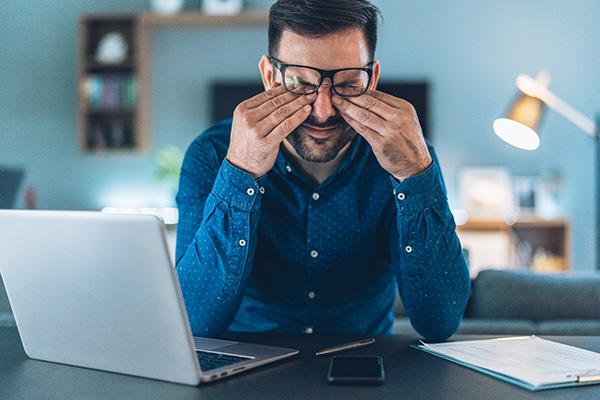 Joven empresario cansado trabajando desde casa