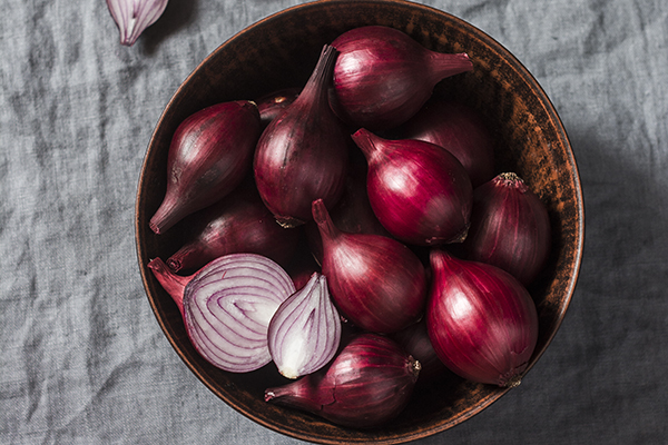 Red onions in a ceramic bowl