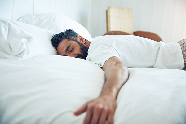 Man lying face down in bed sleeping.