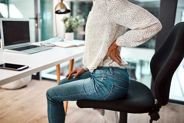 Woman sitting with aching lower back