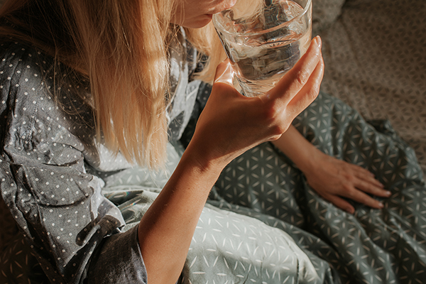Woman drinking water sitting in bed