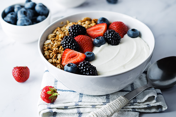 Greek yogurt, nuts, granola, berries in a bowl.