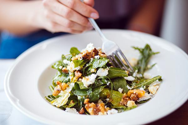 Woman eating a green salad