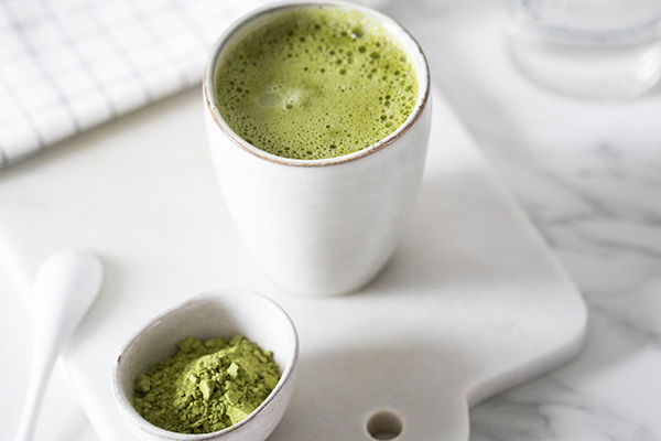 Cup of matcha tea and bowl of matcha powder