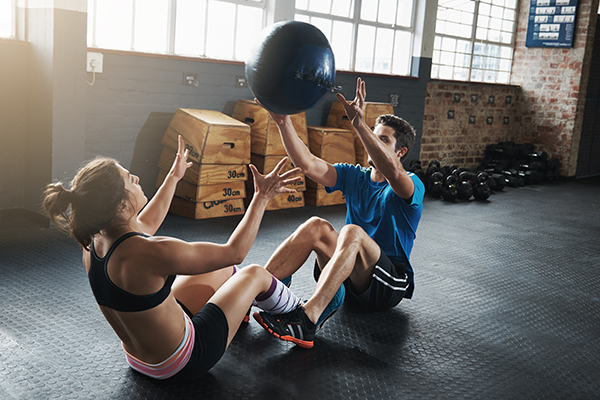 Man and woman throwing a medicine ball back and forth
