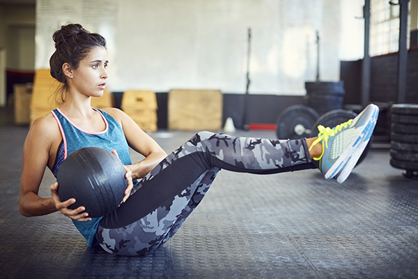 Woman exercising with medicine ball in gym.