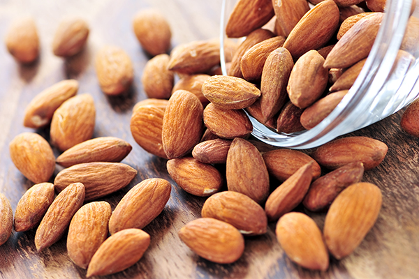 Raw almonds spilling out of small glass bowl