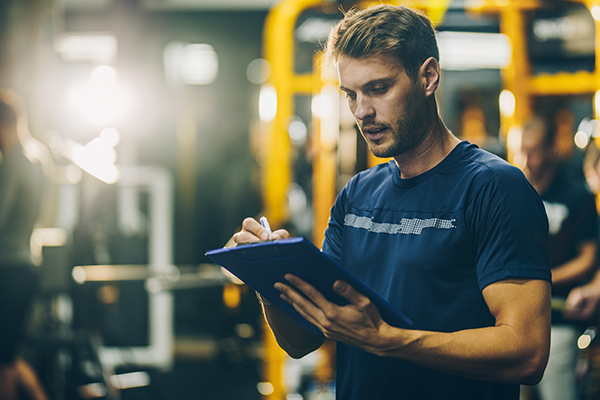 Man writing in fitness journal at gym