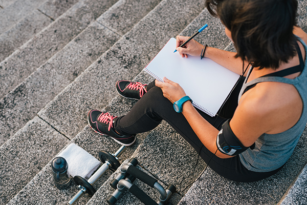 Woman writing in fitness journal outside