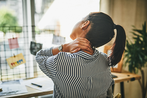 Woman rubbing her neck while working from home