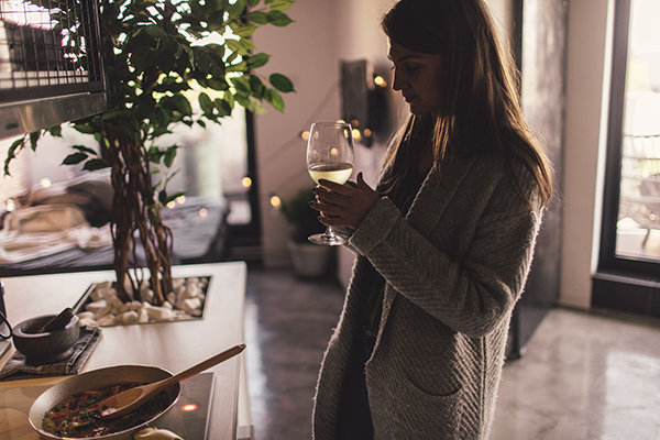 Woman drinking wine alone at home
