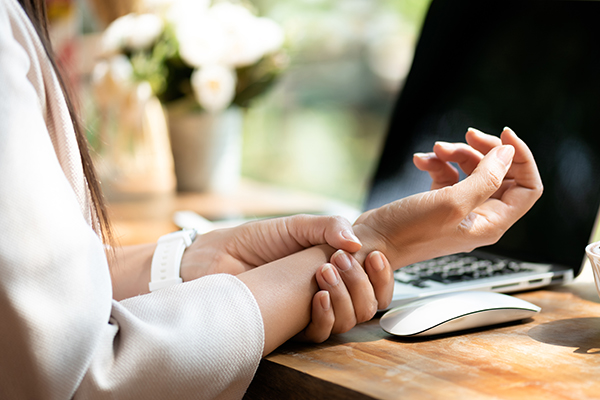 Woman holding her wrist pain from using computer.