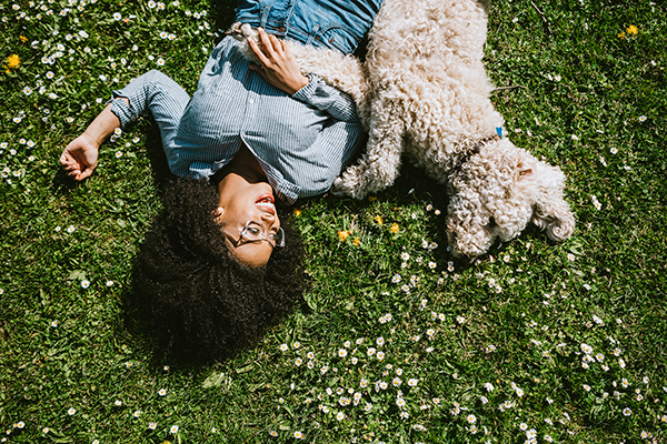 Woman lying in the grass with her dog