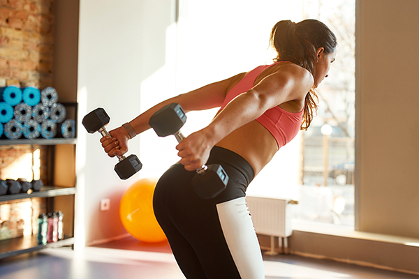Young athletic woman working out using dumbbells in gym.