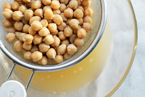 Cooked chickpeas draining aquafaba