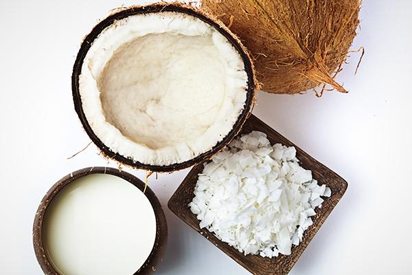 Vista superior de coco abierto, leche de coco y coco rallado