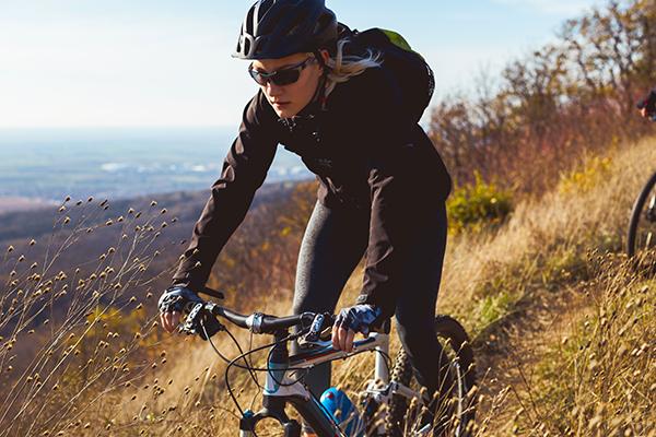 Woman mountain biker ascends meadow.