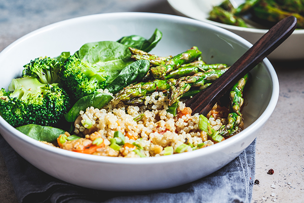 Bowl with quinoa, broccoli, asparagus in a bowl.
