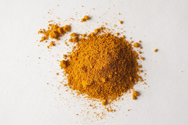 A pile of turmeric, shot in white