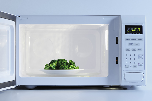 A plate of broccoli in the microwave.