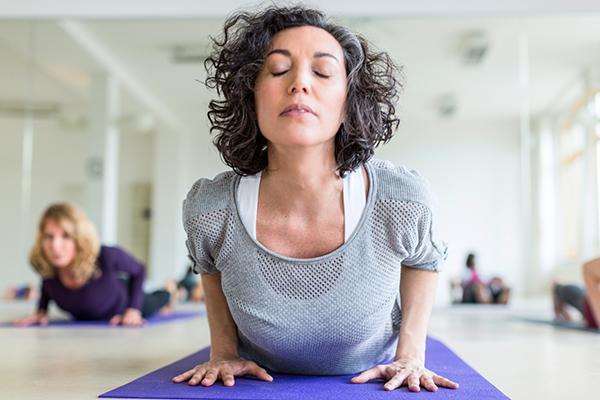 Mature women stretching on yoga mat.