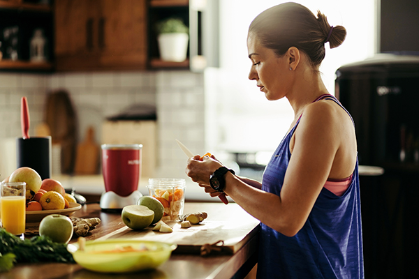 Woman making a healthy smoothie and slicing fresh fruit in the kitchen.