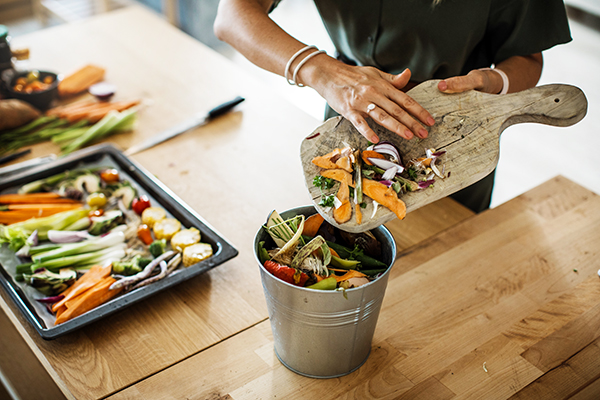 A woman puts leftover vegetables in a compost pail