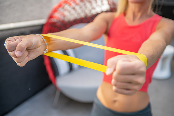 Woman exercising at home with resistance band