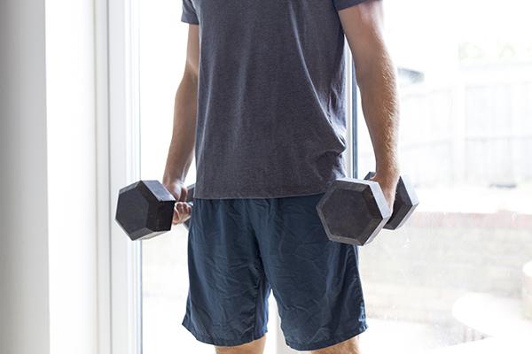 Shot of a man lifting weights at home