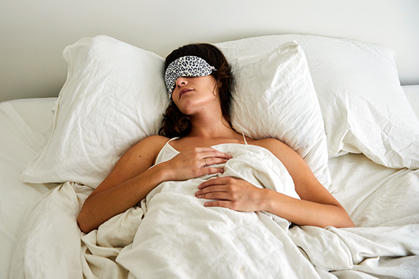 Woman lying in bed with eye mask
