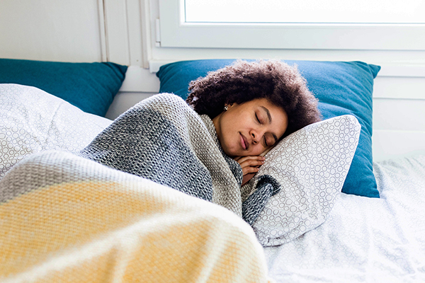 Woman sleeping in bed under blankets