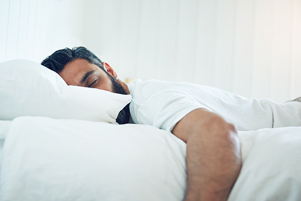 man lying in bed on his stomach