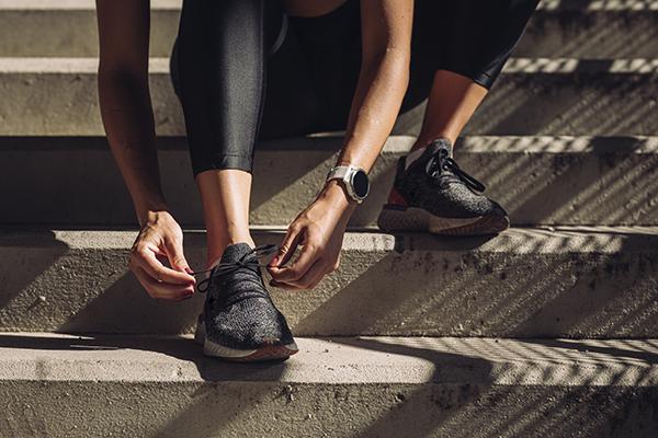 Female runner tying shoelaces on sneakers.