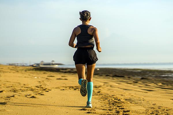 Woman running on beach wearing compression socks