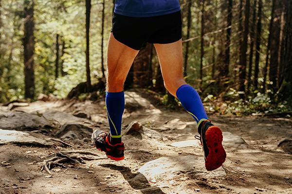 Man trail running wearing compression socks