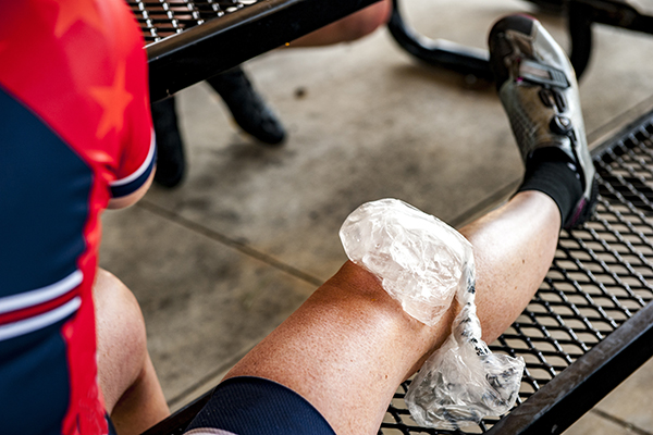 An ice pack on a woman's knee during a break from a bike ride