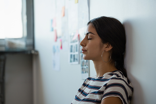 Tired young woman leaning on wall in a office