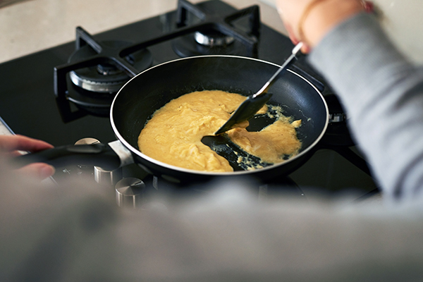 Person stirring scrambled eggs in pan