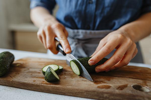 Woman slicing a cucumber on cutting board